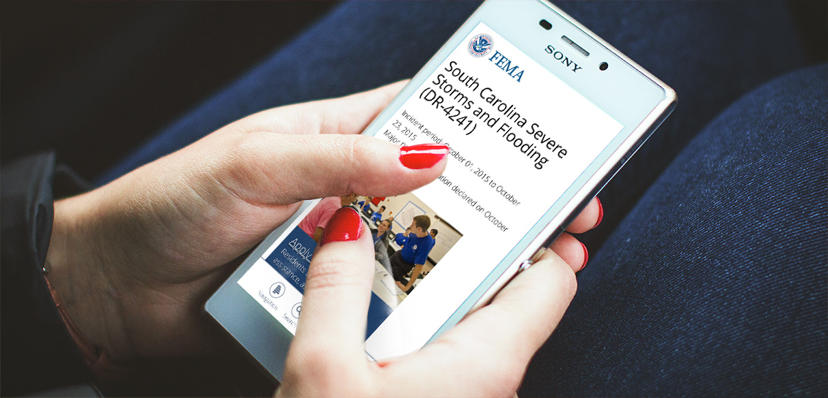 Image of hands browsing FEMA website on mobile device